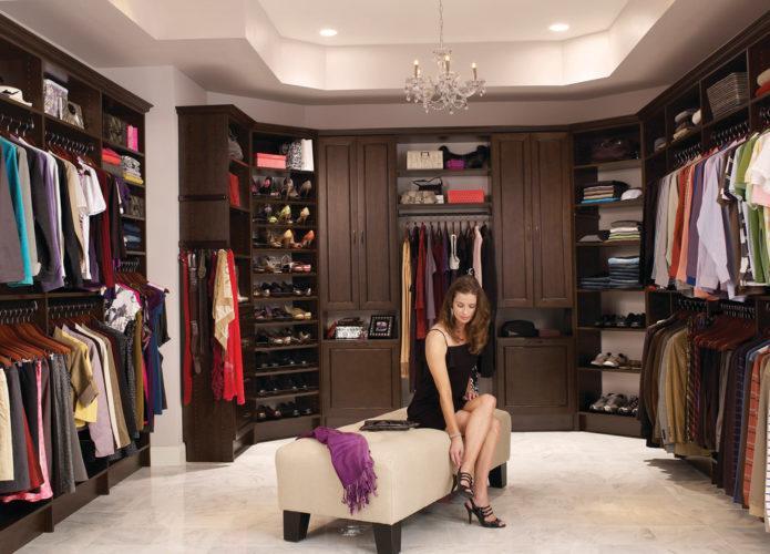 Девушка сидит в большой гардеробной
