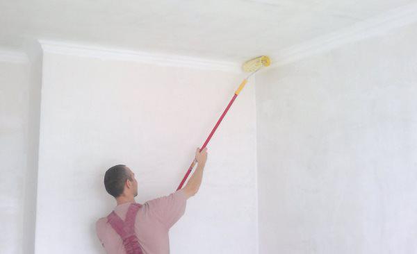 Мужчина наносит грунтовку на потолок