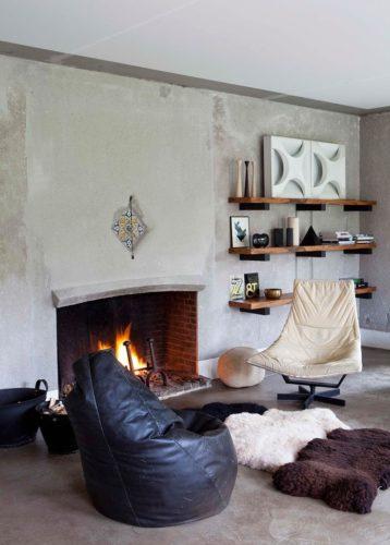 Гостиная с камином, креслами и меховыми ковриками