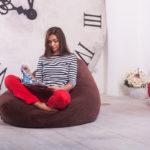 Девушка сидит в комнате на мягком кресле