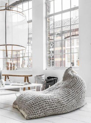 Гостиная с большими окнами и вязаным бескаркасным креслом