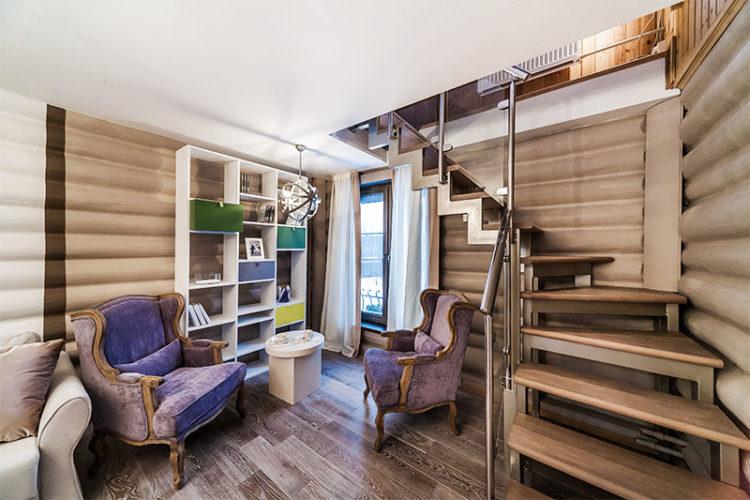 Небольшая гостиная и деревянная лестница на второй этаж