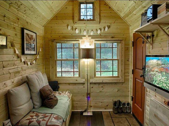 Небольшая комната с мебелью и телевизоров в мансарде