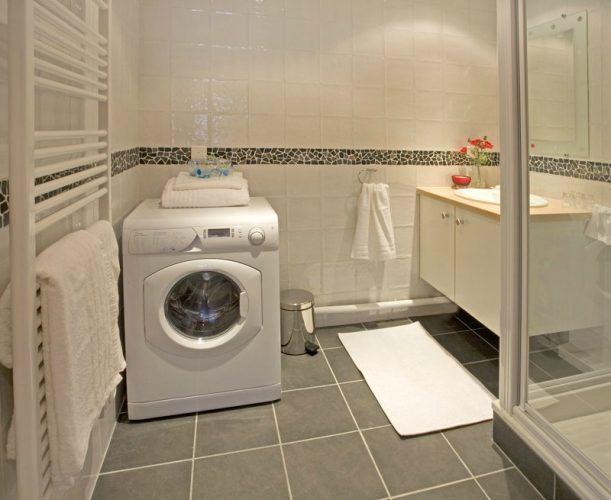 Просторная ванная комната с раковиной, душевой кабиной и стиральной машиной