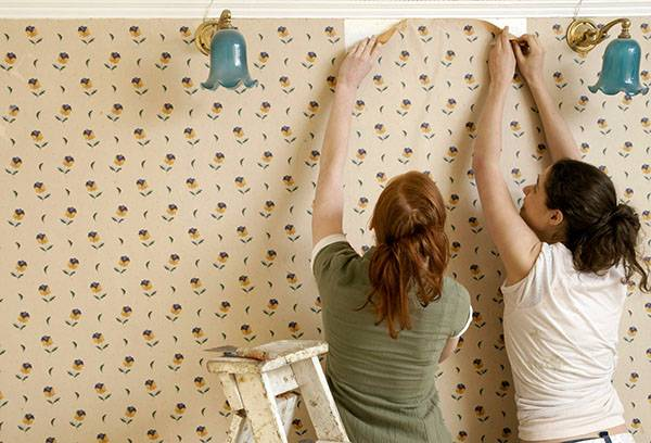 Две девушки срывают со стени обои