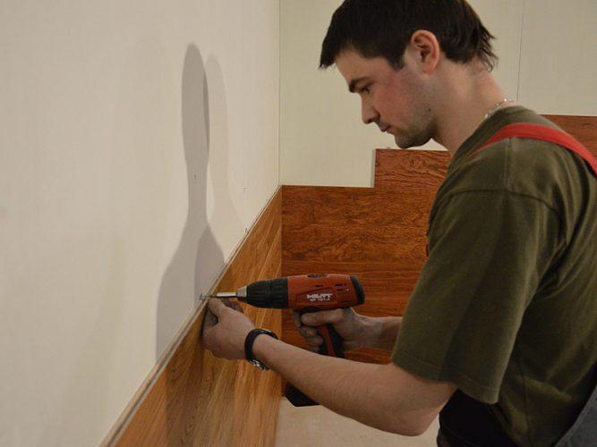 Мастер крепит МДФ-панели саморезами к стене