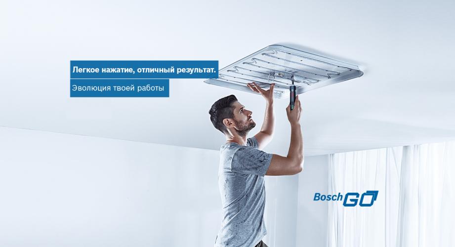 Мастер прикручивает светильник к потолку отверткой Bosch GO