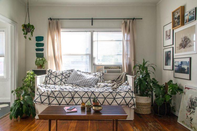 Светлая комната с диваном и растениями на полу