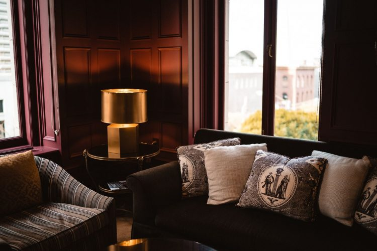 Бордовая гостиная с контрастными подушками и золотой настольной лампой
