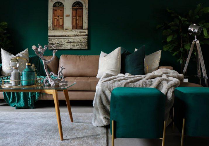 Изумрудная гостиная обыграна контрастными светлыми подушками, золотом и прозрачным стеклом