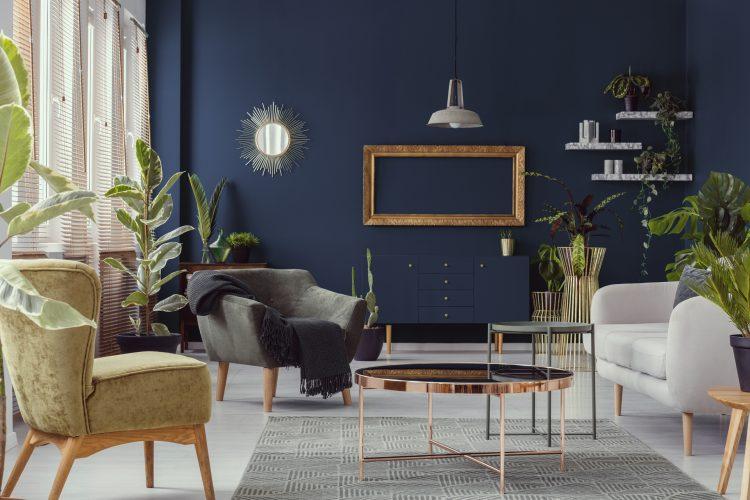 Насыщенный синий цвет стен контрастирует со светлым полом, в качестве акцентов — золото, зеркало и свет