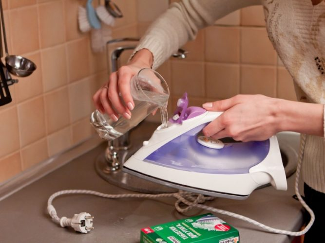 женщина чистит утюг от накипи